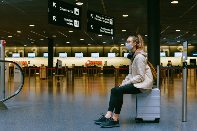 Girl waiting on suitcase to travel in Covid